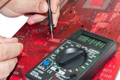 Ο επισκευαστής καθορίζει τον τυπωμένο πίνακα κυκλωμάτων Στοκ εικόνες με δικαίωμα ελεύθερης χρήσης