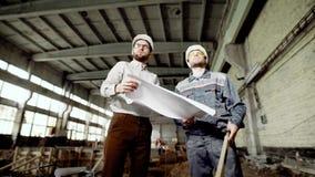 Ο επιστάτης εξηγεί στον εργαζόμενο τη δυνατότητα μια αλλαγή στο εργοτάξιο, όπου το παλαιό εργοστάσιο είναι απόθεμα βίντεο