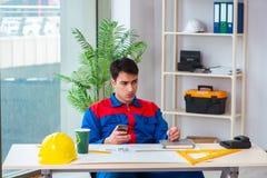 Ο επιστάτης που εξετάζει το σχέδιο κατασκευής Στοκ Φωτογραφίες