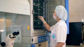 Ο επιστήμονας παίρνει το δείγμα ιών από τον ιατρικό ψυκτήρα φιλμ μικρού μήκους