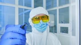 Ο επιστήμονας στο προστατευτικό κοστούμι επισύρει την προσοχή τους χημικούς τύπους στο γυαλί απόθεμα βίντεο