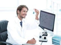 Ο επιστήμονας στο χημικό εργαστήριο εξετάζει μια φιάλη με μια ουσία στοκ φωτογραφία με δικαίωμα ελεύθερης χρήσης
