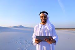 Ο επιτυχής αραβικός επιχειρηματίας κρατά στα χέρια και χρησιμοποιεί την ταμπλέτα, s Στοκ εικόνες με δικαίωμα ελεύθερης χρήσης