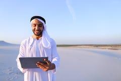 Ο επιτυχής αραβικός επιχειρηματίας κρατά στα χέρια και χρησιμοποιεί την ταμπλέτα, s Στοκ Φωτογραφία