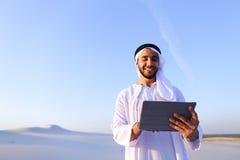 Ο επιτυχής αραβικός επιχειρηματίας κρατά στα χέρια και χρησιμοποιεί την ταμπλέτα, s Στοκ φωτογραφία με δικαίωμα ελεύθερης χρήσης