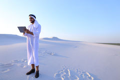 Ο επιτυχής αραβικός επιχειρηματίας κρατά στα χέρια και χρησιμοποιεί την ταμπλέτα, s Στοκ Εικόνες