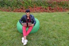 Ο επιτυχής αραβικός νέος επιχειρηματίας κάθεται με το lap-top στην έδρα, S Στοκ εικόνες με δικαίωμα ελεύθερης χρήσης