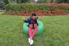 Ο επιτυχής αραβικός νέος επιχειρηματίας κάθεται με το lap-top στην έδρα, S Στοκ Φωτογραφία