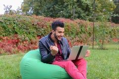 Ο επιτυχής αραβικός νέος επιχειρηματίας κάθεται με το lap-top στην έδρα, S Στοκ Εικόνες