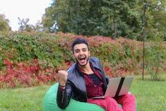 Ο επιτυχής αραβικός νέος επιχειρηματίας κάθεται με το lap-top στην έδρα, S Στοκ φωτογραφία με δικαίωμα ελεύθερης χρήσης
