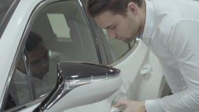 Ο επιτυχής επιχειρηματίας επιθεωρεί το πρόσφατα αγορασμένο αυτοκίνητο από τη εμπορία αυτοκινήτων Αίθουσα εκθέσεως αυτοκινήτων Ένν απόθεμα βίντεο
