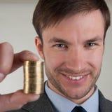 Ο επιτυχής επιχειρηματίας κρατά έναν σωρό των νομισμάτων μπροστά από τον Στοκ εικόνες με δικαίωμα ελεύθερης χρήσης