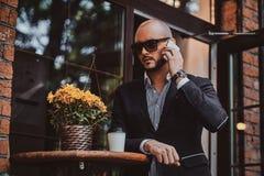 Ο επιτυχής επιχειρηματίας μιλά τηλεφωνικώς καθμένος στο coffeeshop στοκ φωτογραφίες με δικαίωμα ελεύθερης χρήσης