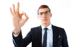 Ο επιτυχής επιχειρηματίας στα γυαλιά και το κοστούμι παρουσιάζει ΕΝΤΑΞΕΙ isol χειρονομίας στοκ εικόνες