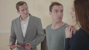Ο επιτυχής κτηματομεσίτης λέει για το νέο σπίτι σε ένα νέο χαριτωμένο παντρεμένο ζευγάρι Ευτυχείς άνδρας και γυναίκα που κοιτάζου απόθεμα βίντεο