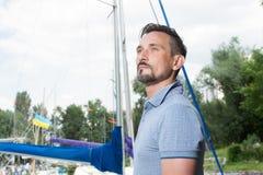 Ο επιτυχής νέος επιχειρηματίας απολαμβάνει το ελεύθερο χρόνο στη μαρίνα Πορτρέτο ιστιοπλοών με τη βάρκα στοκ εικόνες με δικαίωμα ελεύθερης χρήσης