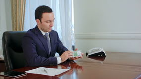 Ο επιτυχής νέος επιχειρηματίας μετρά τους ευρο- λογαριασμούς μιλώντας με το συνάδελφο στο γραφείο φιλμ μικρού μήκους