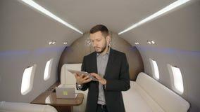 Ο επιτυχής νέος επιχειρηματίας χρησιμοποιεί την ταμπλέτα που στέκεται στο εσωτερικό αεροπλάνων επιχειρηματίας φιλμ μικρού μήκους