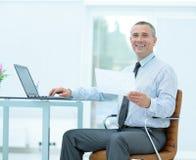 Ο επιτυχής χαμογελώντας επιχειρηματίας με τα έγγραφα κάθεται Στοκ εικόνα με δικαίωμα ελεύθερης χρήσης