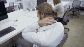 Ο επιχειρηματίας έχει έναν πόνο λαιμών κατά τη διάρκεια της εργασίας στο γραφείο φιλμ μικρού μήκους