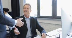 Ο επιχειρηματίας δίνει το επιχειρηματικό σχέδιο εκθέσεων να διευθύνει με τη χειραψία ενώ ομάδα businespeople που λειτουργεί δημιο φιλμ μικρού μήκους