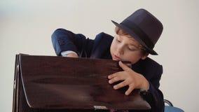Ο επιχειρηματίας αγοριών βγάζει ένα πακέτο των τραπεζογραμματίων εκατό-δολαρίων από το χαρτοφύλακά του φιλμ μικρού μήκους