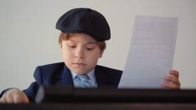 Ο επιχειρηματίας αγοριών παιδιών κάνει τη γραφική εργασία του στο γραφείο του φιλμ μικρού μήκους
