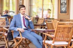 Ο επιχειρηματίας αισθάνεται μια συνεδρίαση ταλαιπωρίας στον καφέ υπαίθριο Στοκ Εικόνες