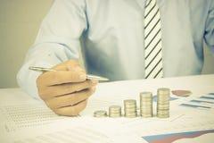 Ο επιχειρηματίας αναλύει και συσσώρευσε των νομισμάτων σε χαρτί γραφικών παραστάσεων, έννοια στην απόκτηση στοκ φωτογραφία με δικαίωμα ελεύθερης χρήσης
