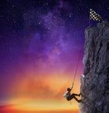 Ο επιχειρηματίας αναρριχείται σε ένα βουνό για να πάρει τη σημαία Επιχειρησιακός στόχος επιτεύγματος και δύσκολη έννοια σταδιοδρο στοκ φωτογραφία