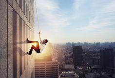 Ο επιχειρηματίας αναρριχείται σε ένα κτήριο με ένα σχοινί Έννοια του προσδιορισμού στοκ φωτογραφία