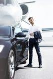 Ο επιχειρηματίας ανοίγει την πόρτα αυτοκινήτων Στοκ Εικόνες