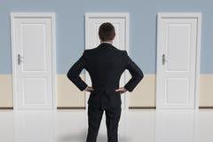 Ο επιχειρηματίας από πίσω λαμβάνει την απόφαση και επιλέγει την πόρτα Στοκ φωτογραφία με δικαίωμα ελεύθερης χρήσης