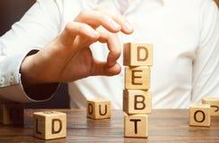Ο επιχειρηματίας αφαιρεί τους ξύλινους φραγμούς με το χρέος λέξης Μείωση ή αναδιάρθρωση του χρέους Ανακοίνωση πτώχευσης Άρνηση να στοκ φωτογραφία με δικαίωμα ελεύθερης χρήσης