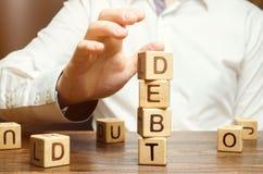 Ο επιχειρηματίας αφαιρεί τους ξύλινους φραγμούς με το χρέος λέξης Μείωση ή αναδιάρθρωση του χρέους Ανακοίνωση πτώχευσης Άρνηση να στοκ εικόνα με δικαίωμα ελεύθερης χρήσης