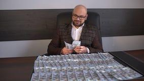 Ο επιχειρηματίας βάζει τα χρήματα και τα δολάρια στον πίνακα Το αρσενικό καταγράφει στα αμερικανικά δολάρια πινάκων Το άτομο κινη απόθεμα βίντεο