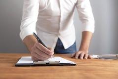 Ο επιχειρηματίας γράφει τα έγγραφα στοκ εικόνα με δικαίωμα ελεύθερης χρήσης