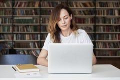 Ο επιχειρηματίας γυναικών που εργάζεται στο lap-top στο ομο-εργαζόμενη γραφείο ή τη βιβλιοθήκη, φαίνεται έξυπνος, ράφια Γνώση και στοκ εικόνες με δικαίωμα ελεύθερης χρήσης