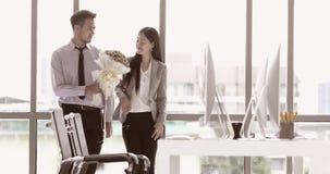 Ο επιχειρηματίας δίνει την ανθοδέσμη στη επιχειρηματία φιλμ μικρού μήκους