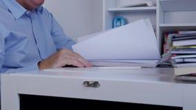 Ο επιχειρηματίας δίνει τις σελίδες καταλόγων ξεφυλλίσματος που ψάχνουν τις πληροφορίες λογιστικής απόθεμα βίντεο