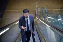 Ο επιχειρηματίας εξετάζει το κινητό τηλέφωνό του Στοκ Εικόνες