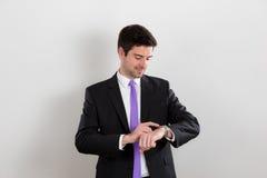 Ο επιχειρηματίας εξετάζει το ρολόι του στοκ εικόνες με δικαίωμα ελεύθερης χρήσης