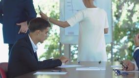 Ο επιχειρηματίας επισύρει την προσοχή ένα διάγραμμα στο whiteboard κατά τη διάρκεια της διάσκεψης φιλμ μικρού μήκους