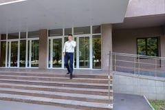 Ο επιχειρηματίας επιχειρησιακών νεαρών άνδρων πηγαίνει εμπρός και χρησιμοποιεί το τηλέφωνο στην πλάτη Στοκ φωτογραφία με δικαίωμα ελεύθερης χρήσης