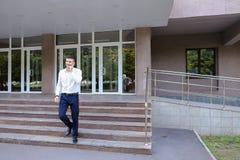 Ο επιχειρηματίας επιχειρησιακών νεαρών άνδρων πηγαίνει εμπρός και χρησιμοποιεί το τηλέφωνο στην πλάτη Στοκ Εικόνα
