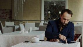 Ο επιχειρηματίας εργάζεται με την ταμπλέτα και τις γραφικές παραστάσεις στον καφέ φιλμ μικρού μήκους