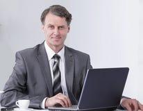 Ο επιχειρηματίας εργάζεται με το lap-top στην αρχή Στοκ εικόνες με δικαίωμα ελεύθερης χρήσης