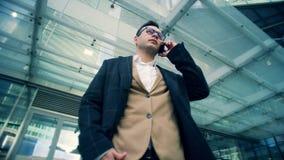 Ο επιχειρηματίας, εταιρικός αρσενικός διευθυντής στέκεται μιλώντας σε ένα τηλέφωνο, κατώτατη άποψη απόθεμα βίντεο