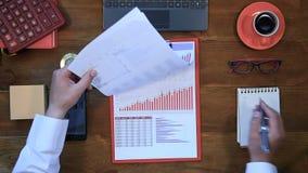 Ο επιχειρηματίας ελέγχει τα διαγράμματα επένδυσης φιλμ μικρού μήκους