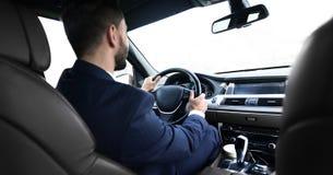 Ο επιχειρηματίας κάθεται στη ρόδα στο αυτοκίνητό του και εξετάζει το δρόμο Στοκ εικόνα με δικαίωμα ελεύθερης χρήσης